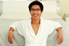 Man in bathrobe leaning on the bed Royalty Free Stock Photography