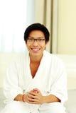 Man in bathrobe sitting on the bed Stock Photos