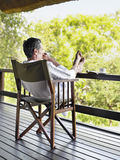 Man In Bathrobe Sitting In Terrace With Feet Up Stock Image