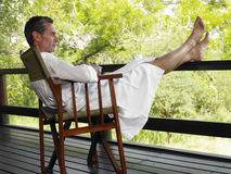 Man In Bathrobe Sitting In Terrace With Feet Up Stock Photo