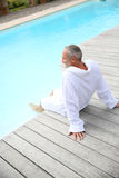 Man in bathrobe sitting on wood deck of pool Stock Photos