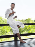 Man In Bathrobe On Terrace Railing With Tea Royalty Free Stock Photography