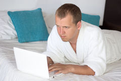 Man in bathrobe using laptop in hotel room Royalty Free Stock Photos