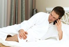 Man in bathrobe. Man in bathrobe using mobile phone in hotel room royalty free stock images