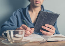 Man in bathrobe using table and taking notes Royalty Free Stock Photos