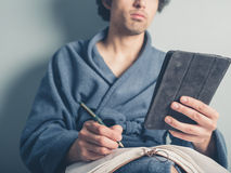 Man in bathrobe using tablet and taking notes Royalty Free Stock Images