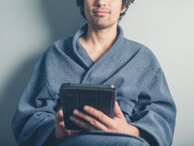 Man in bathrobe using tablet Royalty Free Stock Images