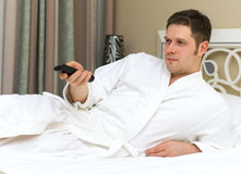 Man in bathrobe watching TV. Royalty Free Stock Image