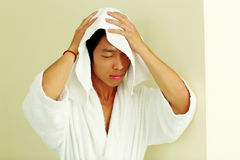 Man in bathrobe wiping face Stock Image