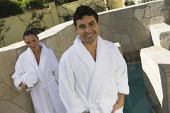 Man In Bathrobe With Woman Holding Towel In The Background Stock Photo