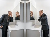 Man in bathroom applying cosmetics Stock Photo
