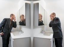 Man in bathroom applying cosmetics Stock Photo