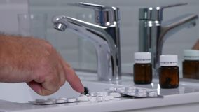 Man in bathroom count and select medical pills drugs vitamins and antibiotics