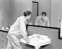 Man in bathroom looking into mirror Royalty Free Stock Photos