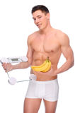 Man with bathroom scales and banana. Full isolated studio picture from a young naked man with underwear and scales and banana Royalty Free Stock Images