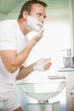Man in bathroom shaving royalty free stock images