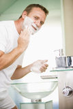 Man in bathroom shaving Stock Photos
