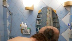 Man shaving with a razor in a van room