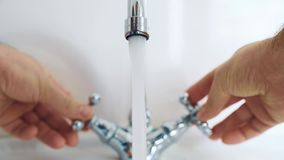 The man in the bathroom with two hands regulates the temperature of the water from the tap