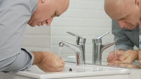 Man in Bathroom Washing His Hands and Face with Fresh Water in Sink stock images