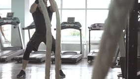 Man with battle rope in functional training fitness gym stock footage