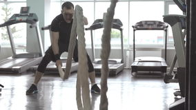 Man with battle rope in functional training fitness gym stock video footage