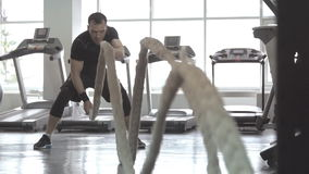 Man with battle rope in functional training fitness gym stock video
