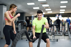 Man with battle ropes exercise in the fitness gym. Female personal trainer motivating young men with battle ropes exercise in the fitness gym royalty free stock photo