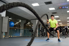 Man with battle ropes exercise in the fitness gym.