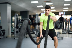 Man with battle ropes exercise in the fitness gym. Young male wearing sportswear Stock Images