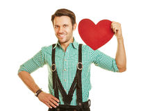 Man in bavaria holding red heart on Stock Photo