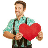 Man in bavaria holding red heart Stock Image
