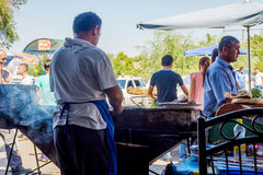 Man bbq shashlik, Uzbekistan. FERGANA, UZBEKISTAN - AUGUST 20: Man grilling meat skewers called shashlik in a restaurant in Fergana. August 2016 Stock Images