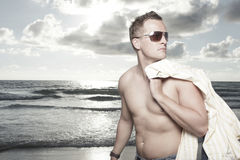 Man on the beach. Young man on the beach holding his shirt over his shoulder Stock Photography