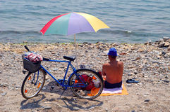 Man on the beach. With umbrella and bike Stock Photo