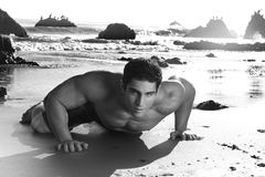 Man on Beach. Fine art black and white photo of a young muscular man crawling on beach Royalty Free Stock Photography