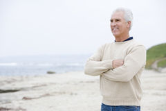 Man at the beach with arms crossed smiling Stock Photos