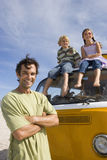 Man on beach with arms crossed by son and daughter (5-9) on roof of camper van, portrait, low angle view Royalty Free Stock Photos