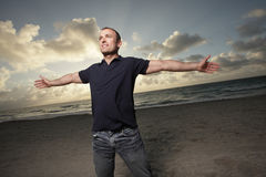 Man on the beach with arms extended Royalty Free Stock Image