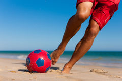 Man on beach balancing soccer ball Stock Image