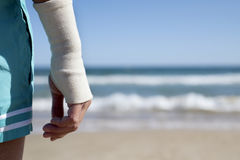 Man on the beach with a bandage in his wrist. Closeup of a young caucasian man in swimsuit on the beach with a bandage in his wrist, in front of the sea, with a stock photography