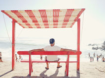 Man on beach bench Stock Images