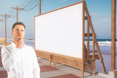 Man with beach billboard. Thoughtful man near empty beach billboard. Advertisement concept. Side view. Mock up, 3D Rendering Royalty Free Stock Image