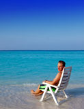 Man in a beach chair at ocean Royalty Free Stock Photos