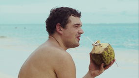Man on the beach drinking from coconut stock video footage
