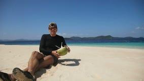 Man on the beach drinking coconut juice stock video