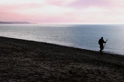 Man on beach at dusk. Silhouetted man with walking stick hiking on beach at dusk Royalty Free Stock Photography