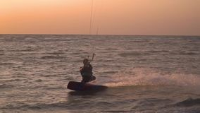A man on the beach is engaged in kitesurfing, slow motion. A man in a diving suit slides on a kitesurf near the shore stock footage