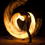 Man on beach with fire. Anonymous man in motion creating fire show on beach in night time Royalty Free Stock Photography
