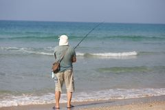 Man on the beach fishing stock photo
